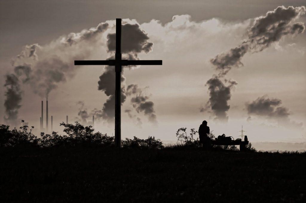 Ein Kreuz vor Industrieschloten mit Rauchentwicklung