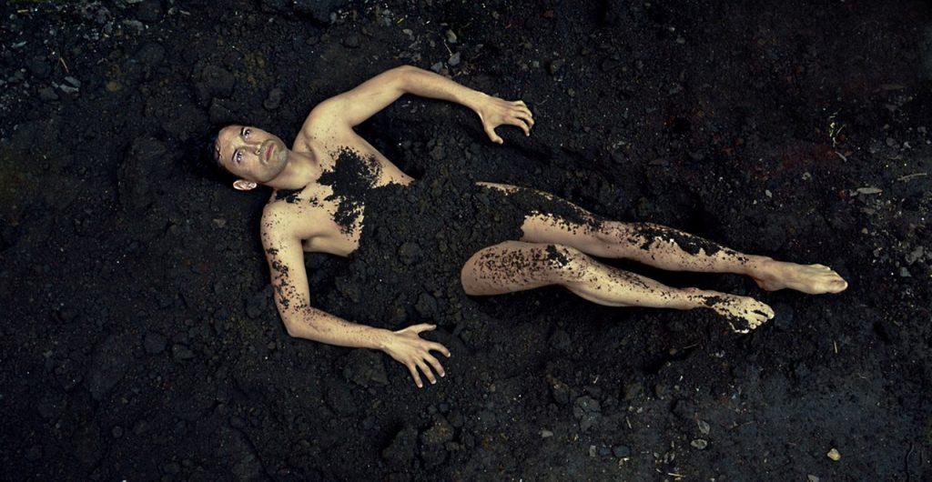 Ein nackter Mann auf Ackerboden, von Erde bedeckt