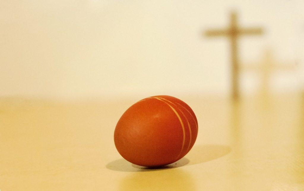 Ein liegendes Hühnerei mit dem Schatten eines Kreuzes im Hintergrund