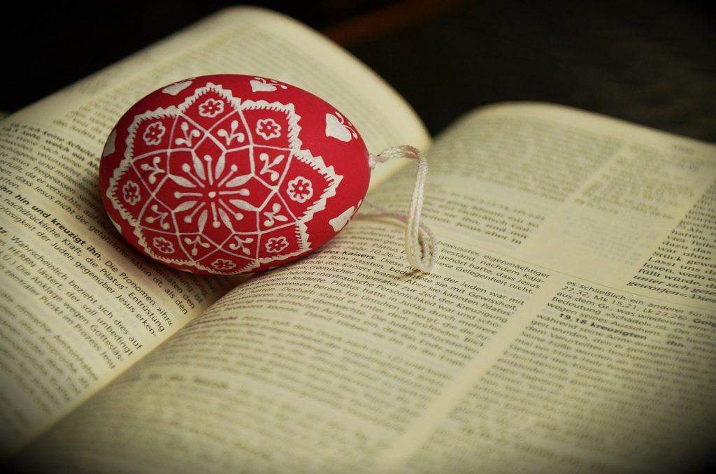 Ein Osterei liegt in der aufgeschlagenen Bibel