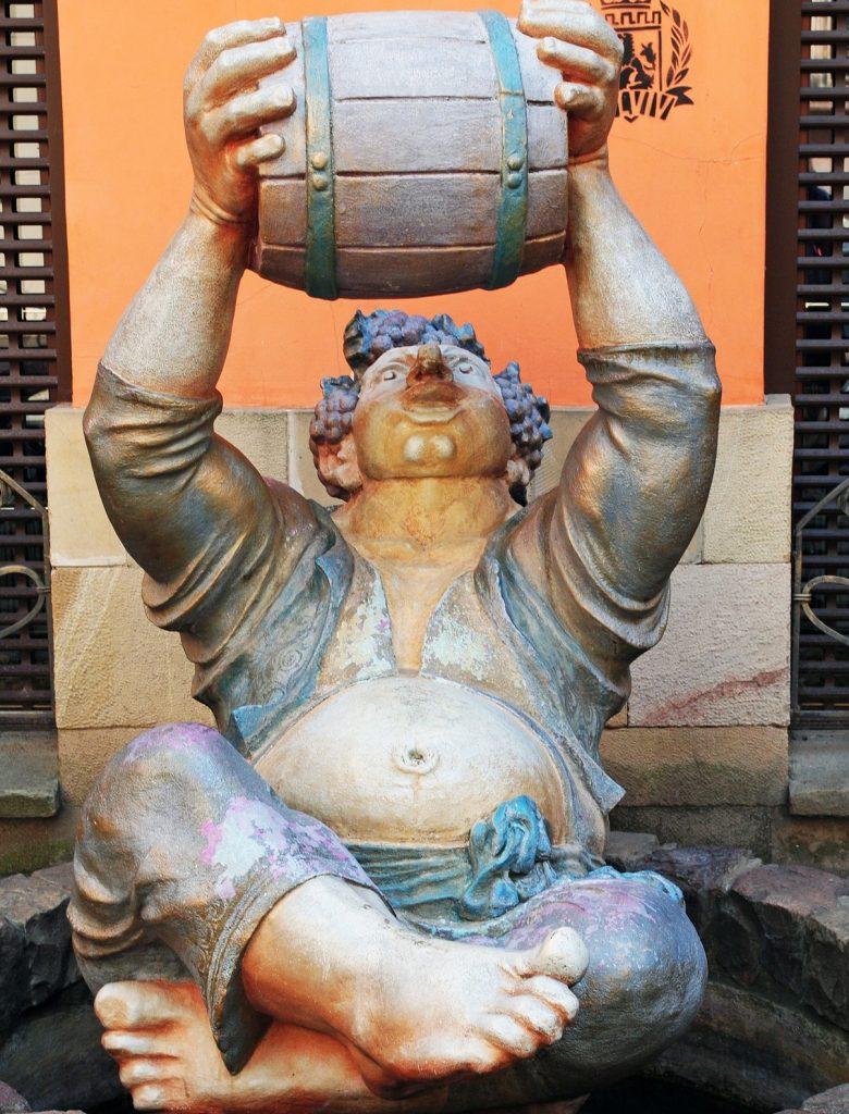 Die Skulptur eines Säufers in Lviv in der Ukraine, der ein Fass über sich hält und den Inhalt in seinen Mund laufen lässt
