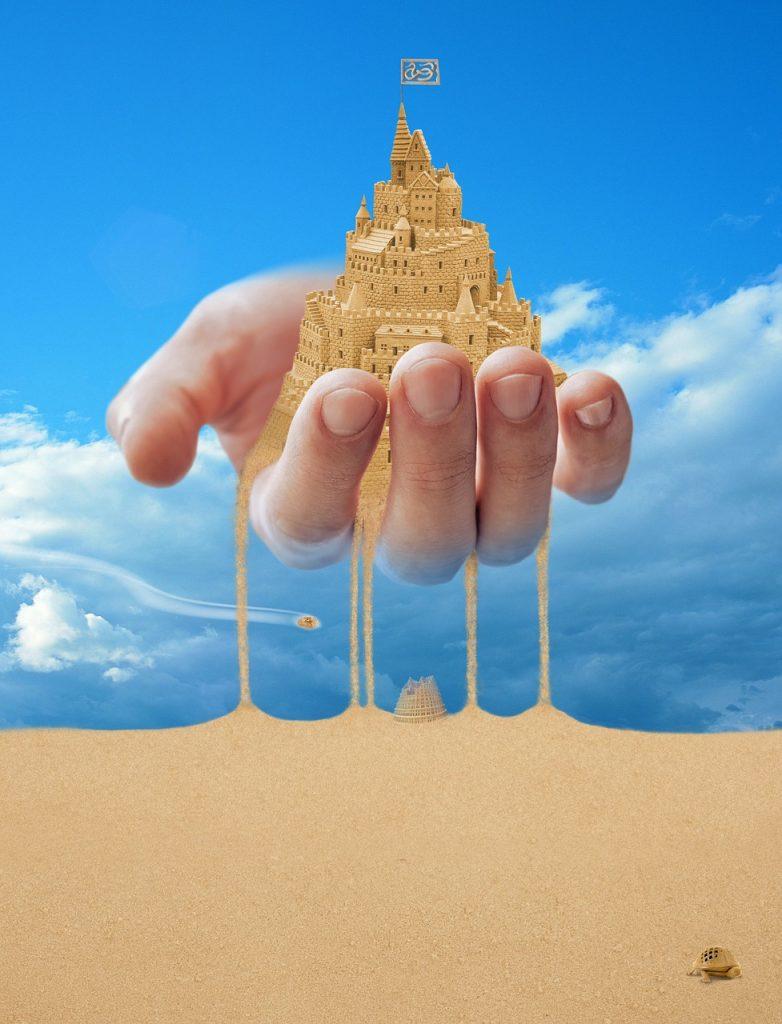 Eine Stadt aus Sand zerrinnt zwischen den Fingern; vorn kriecht eine kleine Schildkröte