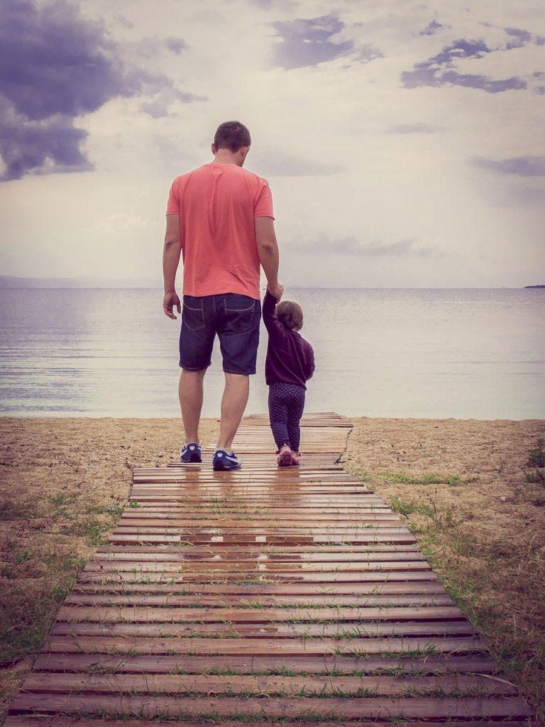 Vater mit Kind an der Hand auf einem Steg, der zum Strand führt