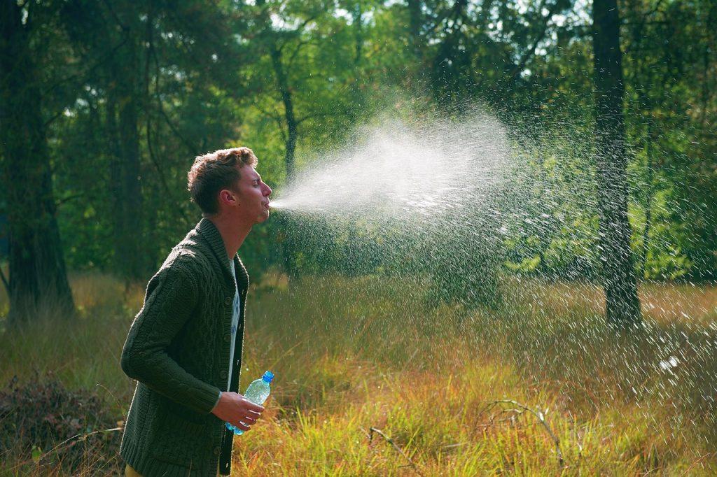 Ein Mann im Wald spuckt Wasser aus, so dass es sprüht