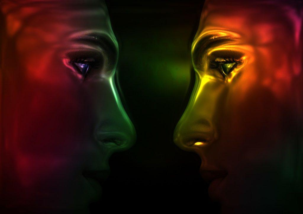 Zwei einander ansehende Gesichter im Streit, wie farbig glühend