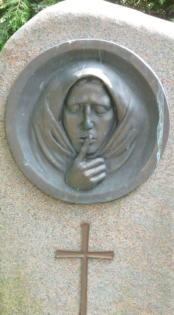 Ein Gesicht mit Kopftuch, geschlossenen Augen und einem Finger auf dem Mund, darunter ein Kreuz