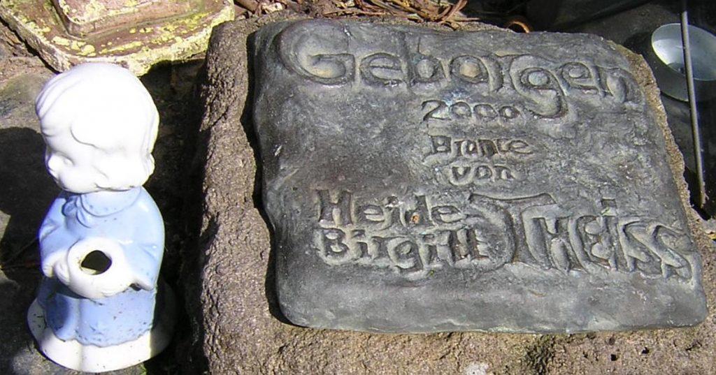 """Die Signaturplatte der Skulptur """"Geborgen - 2000 - Bronce von Heide Birgitt Theiss"""""""