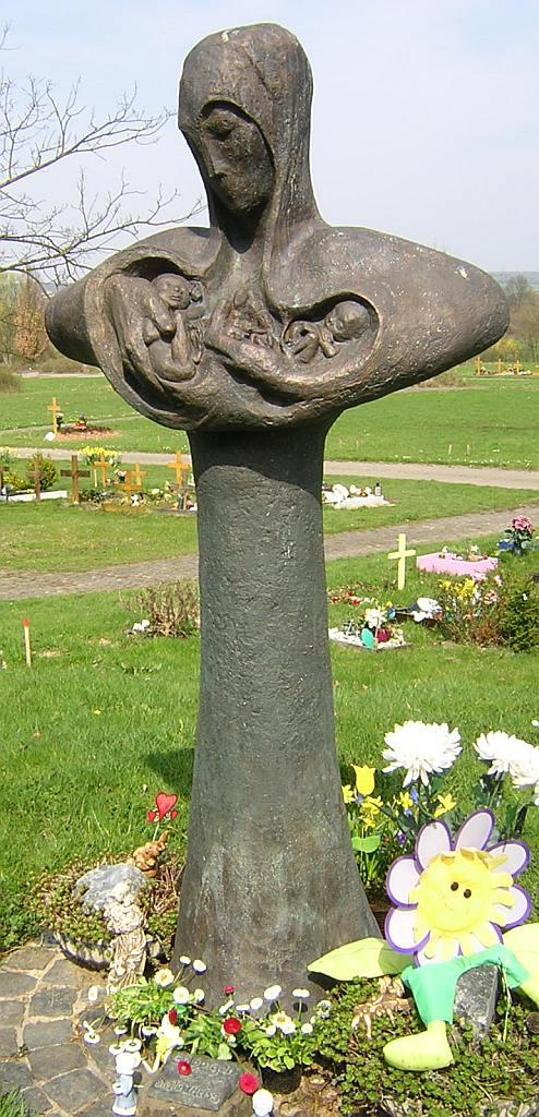 Die Skulptur Geborgen von Heide Birgitt Theiss: eine Mutter, in deren Brust ungeborene Kinder liegen, die sie mit ihren Armen liebevoll umfängt