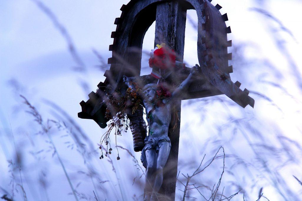Ein Kruzifix mit Überdachung umgeben von Gräsern draußen in der Natur