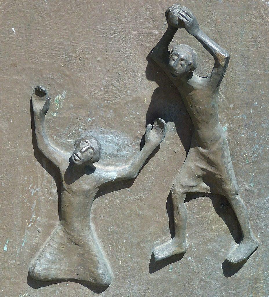 Kain erhebt seine Hände mit einem Stein über Abel, der mit ausgebreiteten Armen und mit dem Rücken zu ihm gewendet vor ihm kniet.