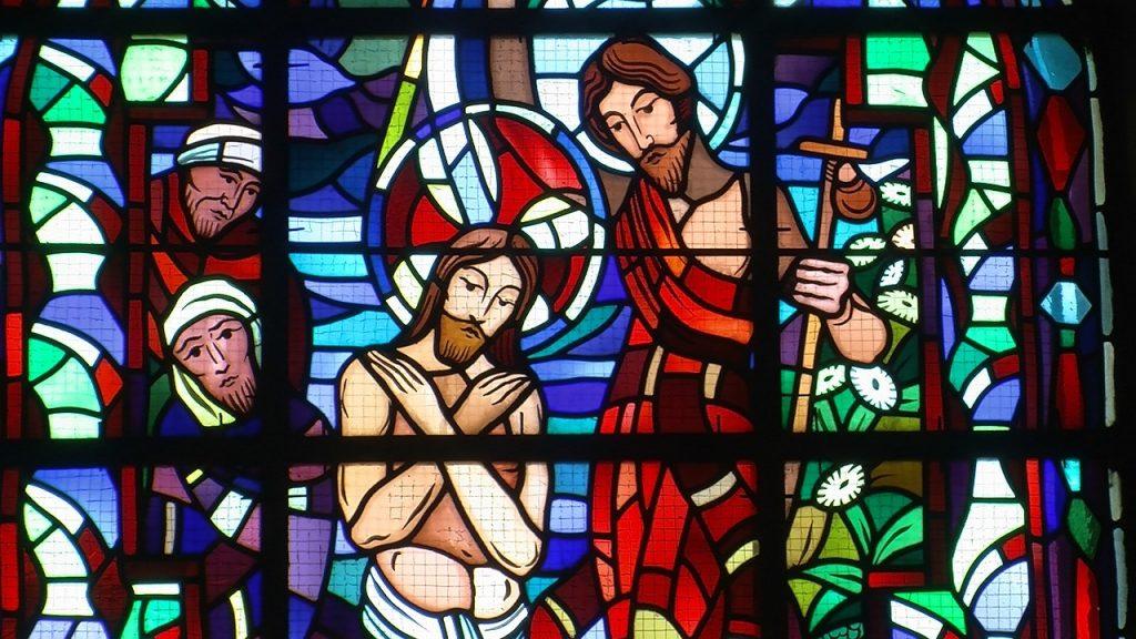 Kirchenfenster: Jesus wird durch Johannes getauft, zwei schauen zu