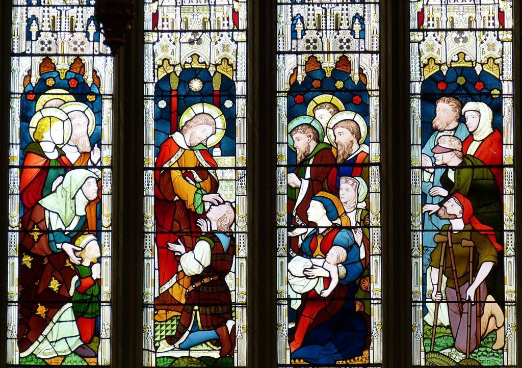Ein vierteiliges Kirchenfenster stellt Jesus als Arzt dar für Blinde und Lahme, und als Freund der Frauen und Kinder