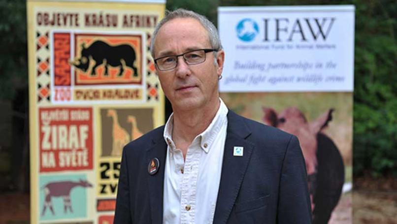 Peter Pueschel vor Plakaten der IFAW