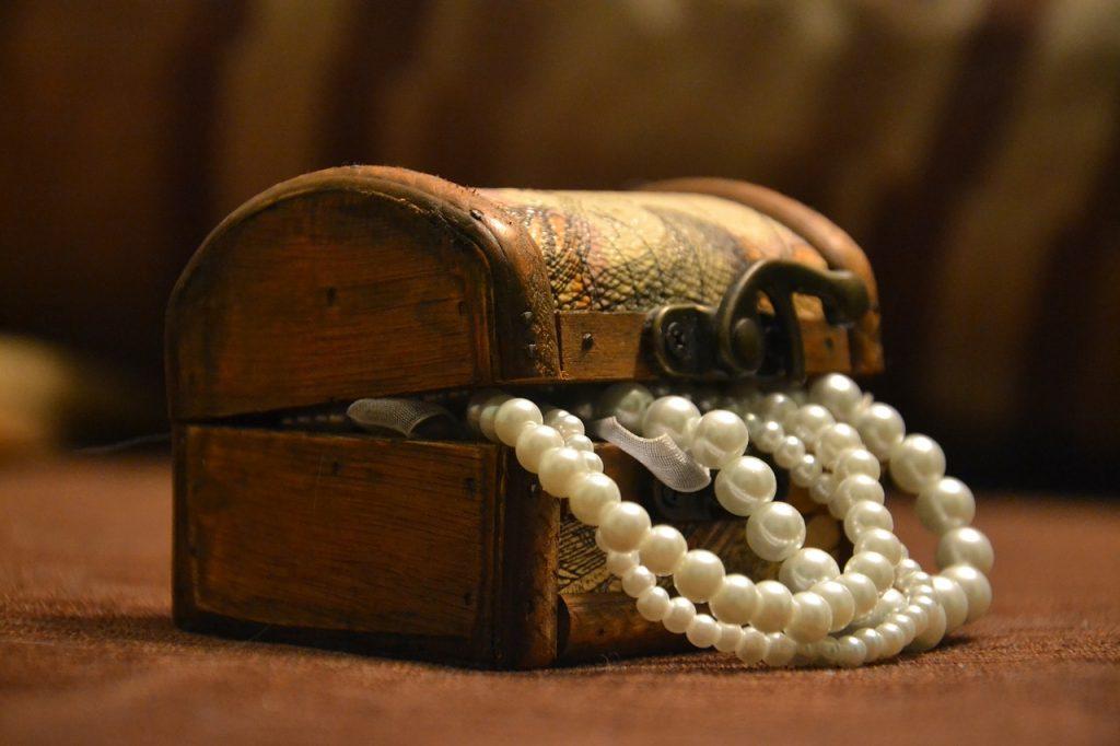 Eine Schatzkiste, aus der Perlenketten herausquellen