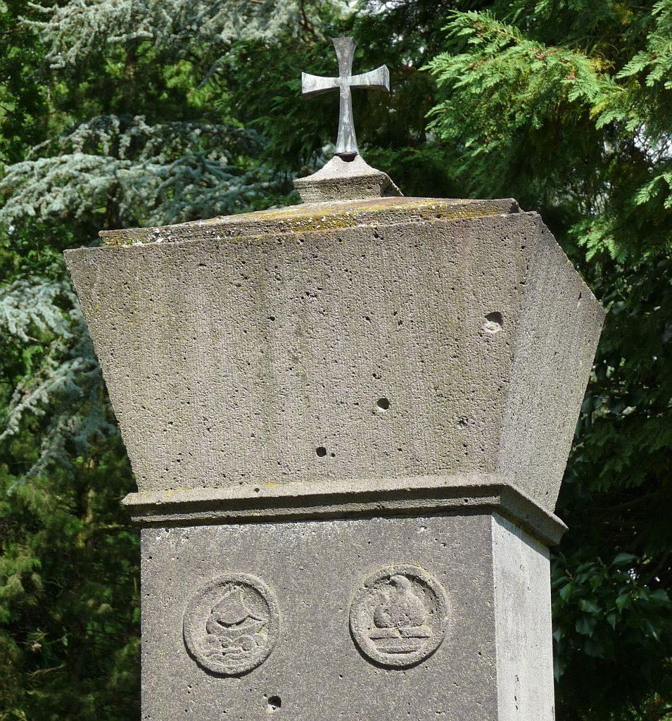 Große Stein-Stele mit Kreuz oben drauf und den Symbolen für Styx und Phönix