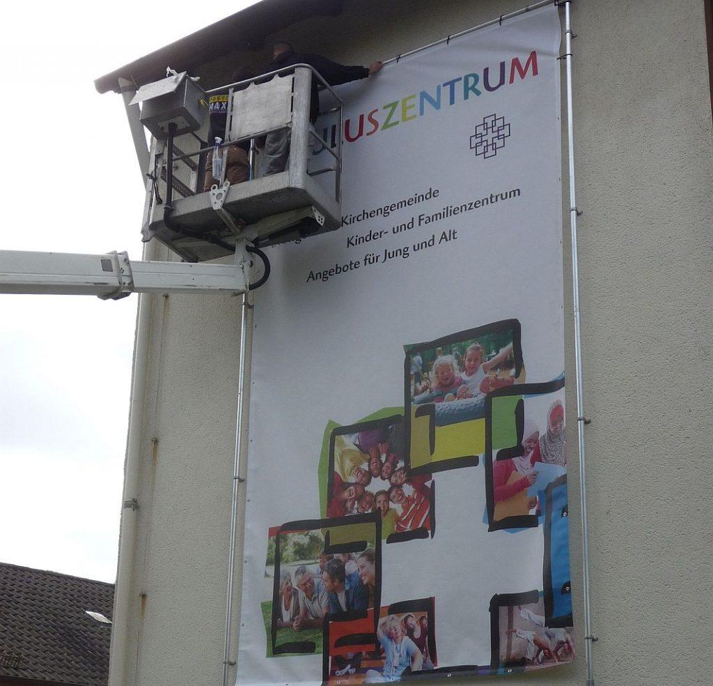 Aufhängung des Banners für das Pauluszentrum an der Wand der evangelischen Pauluskirche Gießen
