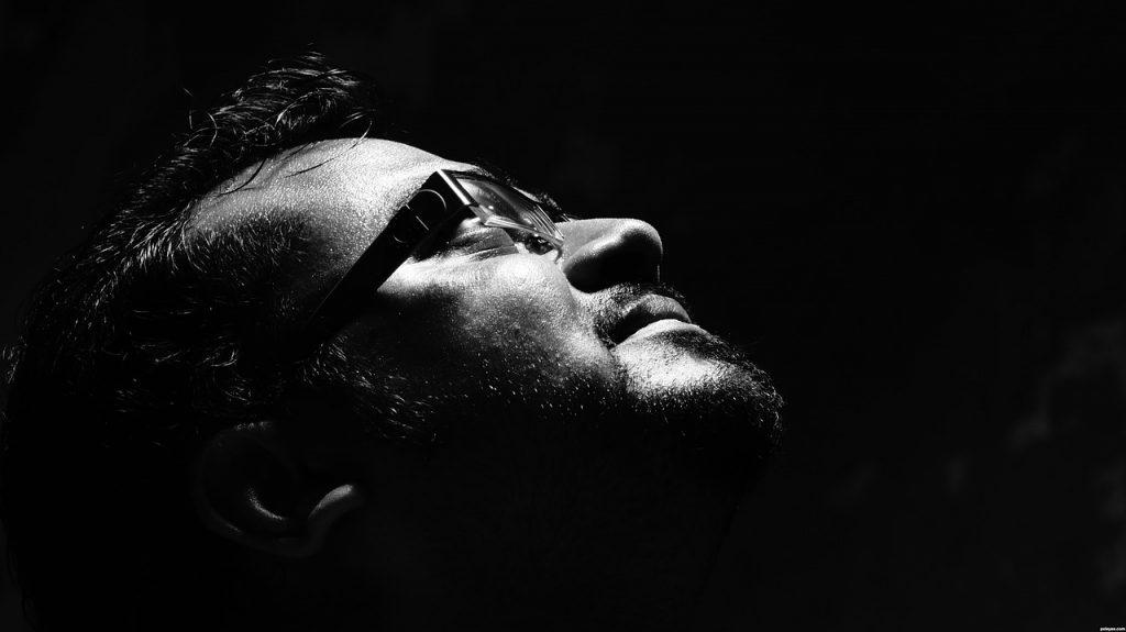 Ein Mann blickt mit ernstem Gesicht nach oben, in völliger Dunkelheit