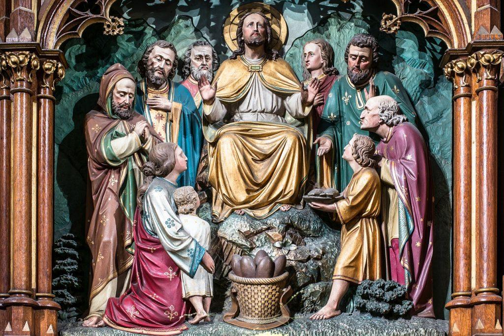 Farbenfrohe Relief-Darstellung: Jesus, umringt von Jüngern, empfängt von einem Kind, um das seine Mutter ihren Arm legt, fünf Brote und zwei Fische