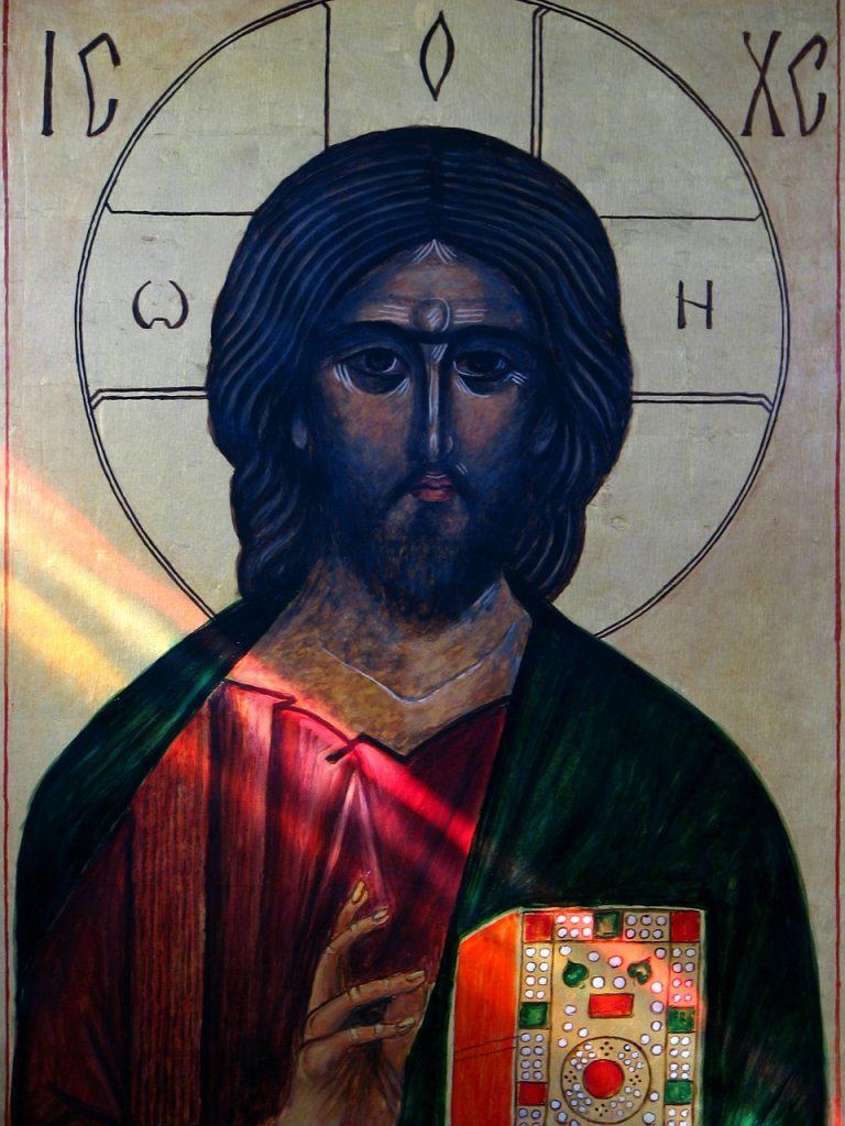 Ikone von Jesus mit dunklem Gesicht und farbigem Buch, farbige Sonnenstrahlen fallen auf das Buch