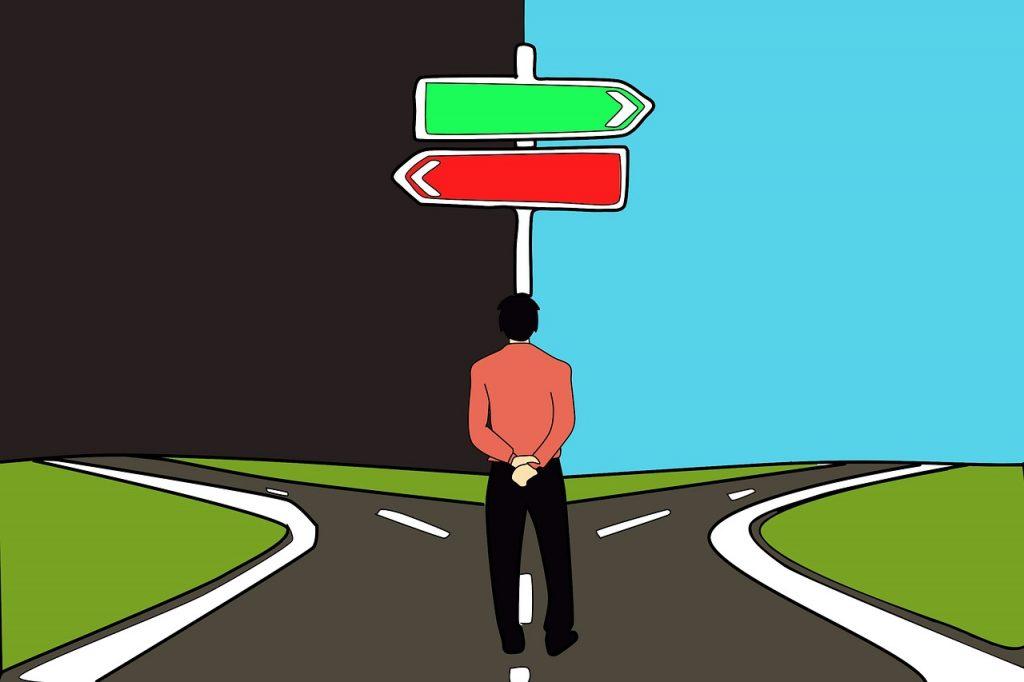 Ein Mann steht vor einer Straßengabelung, nach links führt ein rotes Schild ins Dunkle, nach rechts ein grünes ins Hellblaue
