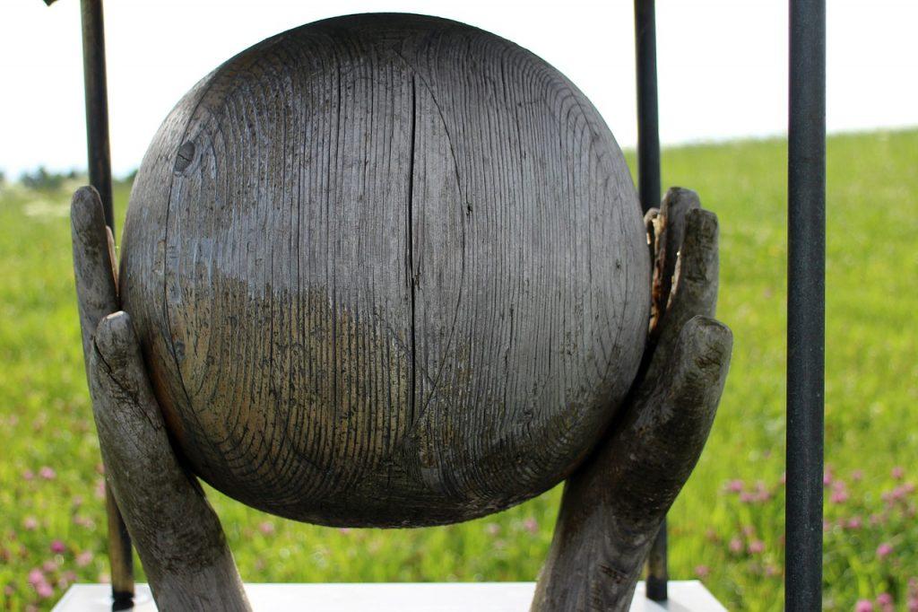 Erdkugel aus Holz, von zwei Händen aus Holz umfangen