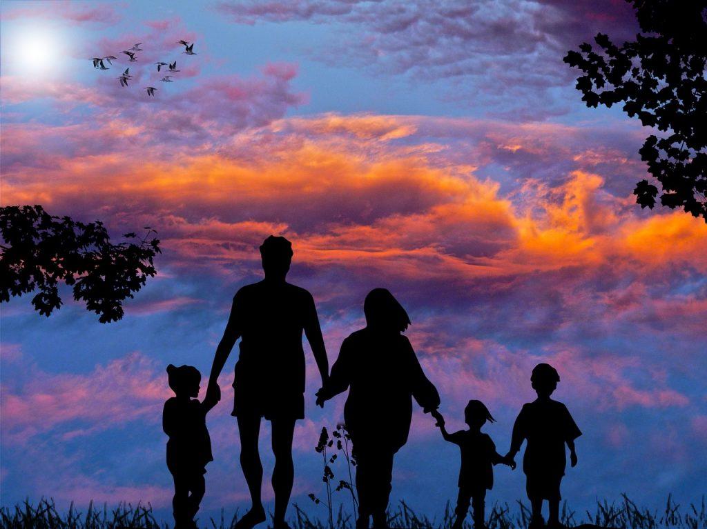 Eine Familie, Eltern mit drei Kindern, unter schönem Abendrot