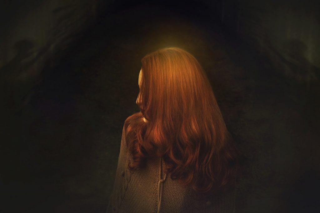 Eine Frau im Profil, das Gesicht von den Haaren verdeckt, steht in der Finsternis