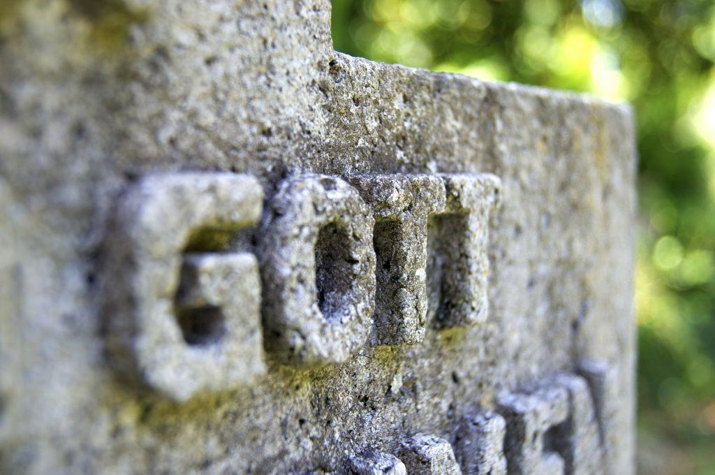"""Der Schriftzug """"GOTT"""" - eingemeißelt auf einem Grabstein"""