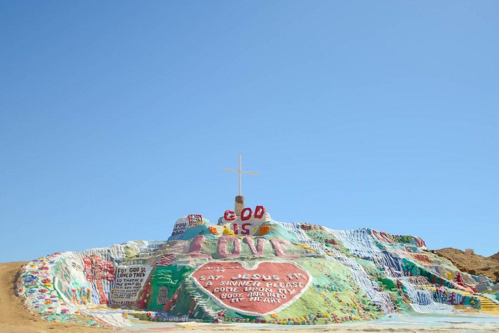 """Eine bunt gestaltete Felsenlandschaft mit frommen Aussagen zur Gnadenpower wie """"Gott ist Liebe"""" und in einem Herz: """"Sag Jesus, ich bin ein Sünder, komm in mein Herz!"""""""