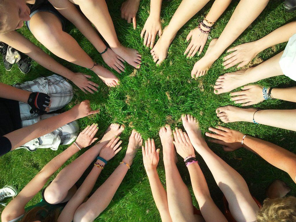 Hände und Füße bilden einen Kreis auf grünem Rasen