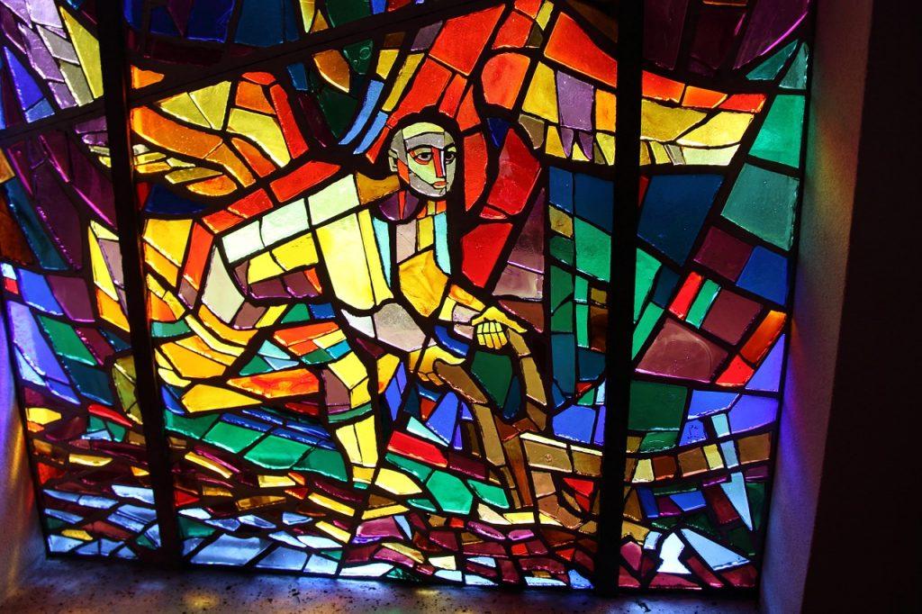 Kirchenfenster: Ein Mann mit leuchtend rot-gelben Engelsflügeln läuft hinter einem Pflug her