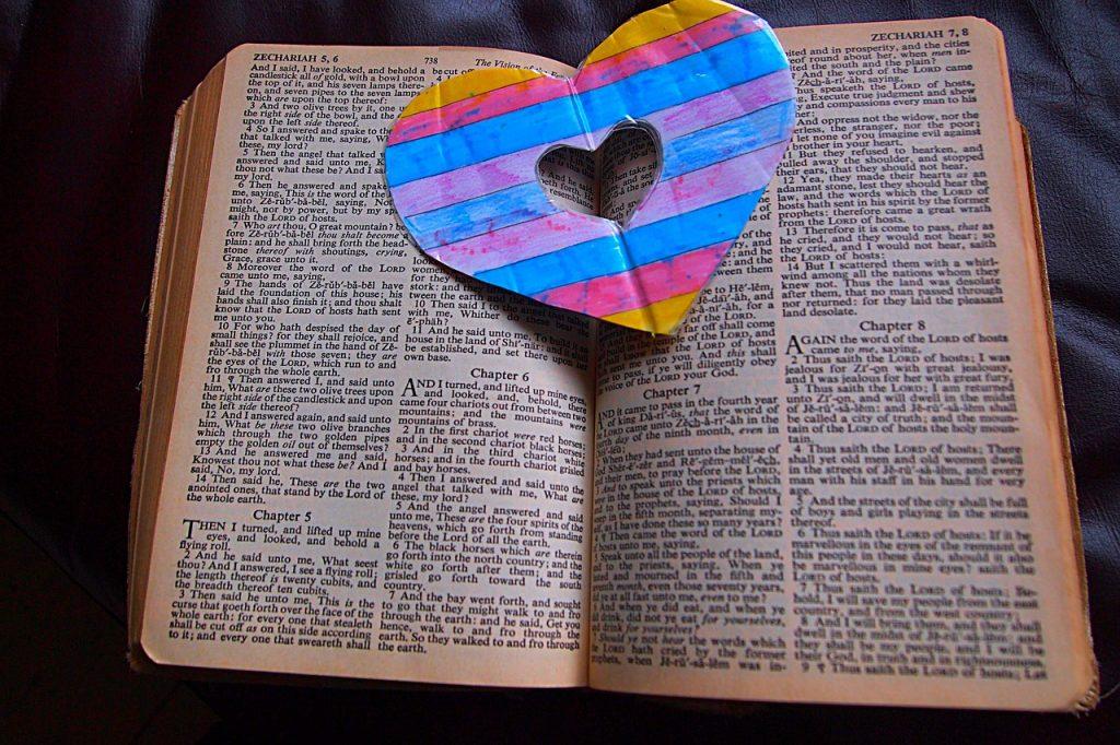 Ein mit bunten Streifen verziertes Herz als Lesezeichen in einer Bibel