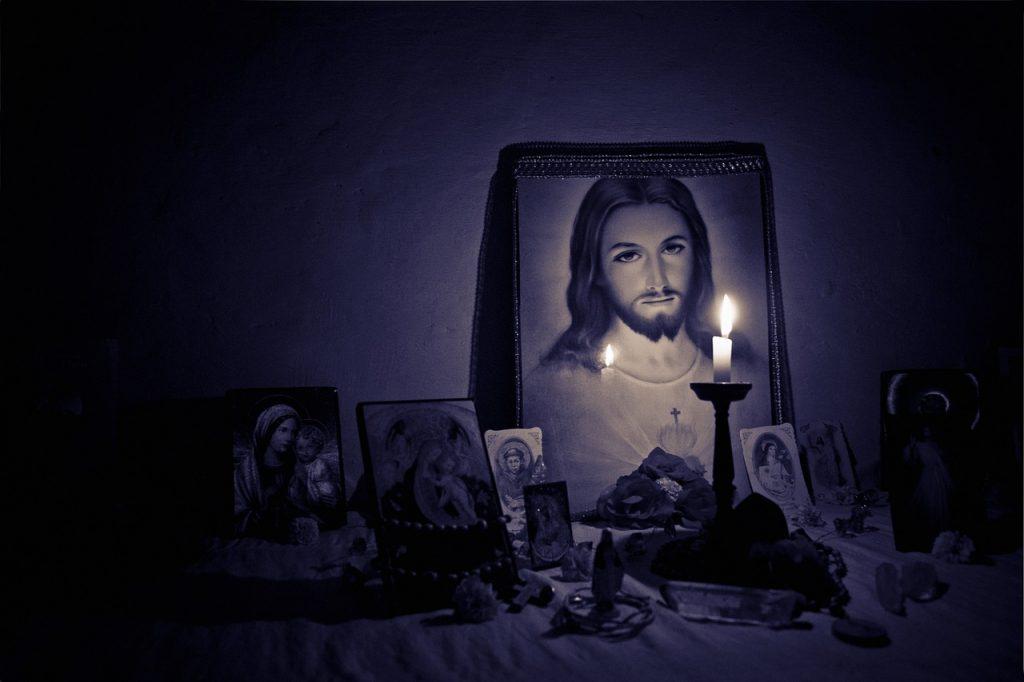 Jesusbild, davor eine Kerze und andere religiöse Bilder und Gegenstände im Halbdunkel