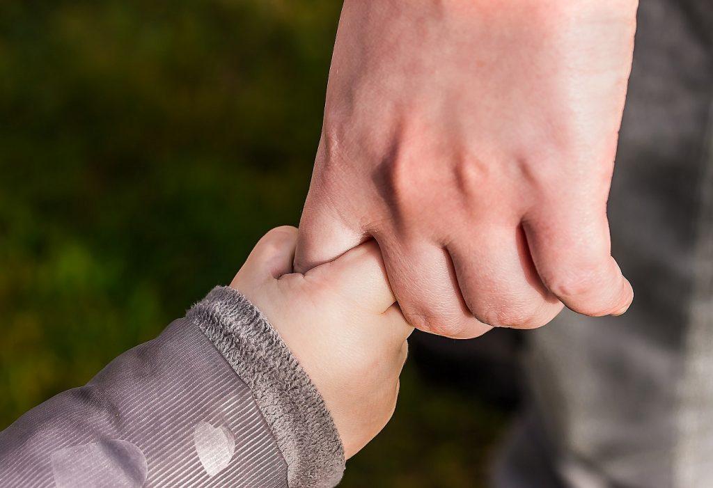 Eine Kinderhand fasst den Finger einer Erwachsenenhand