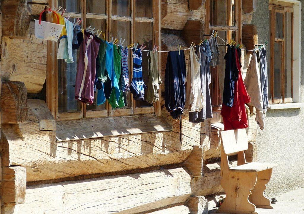 Kleidungsstücke auf einer Wäscheleine vor einem Haus