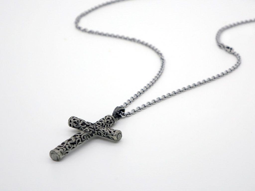Ein Kreuz an einer Halskette liegt auf einer ebenen Fläche