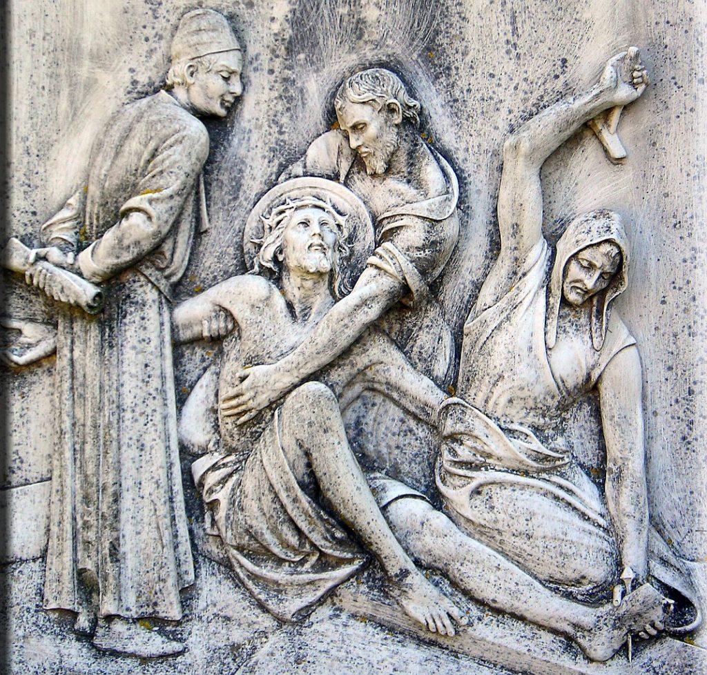Ein römischer Soldat nagelt Jesu Fuß am Kreuz fest, ein jüdischer Schriftgelehrter schaut zu, ein Freund umarmt Jesus