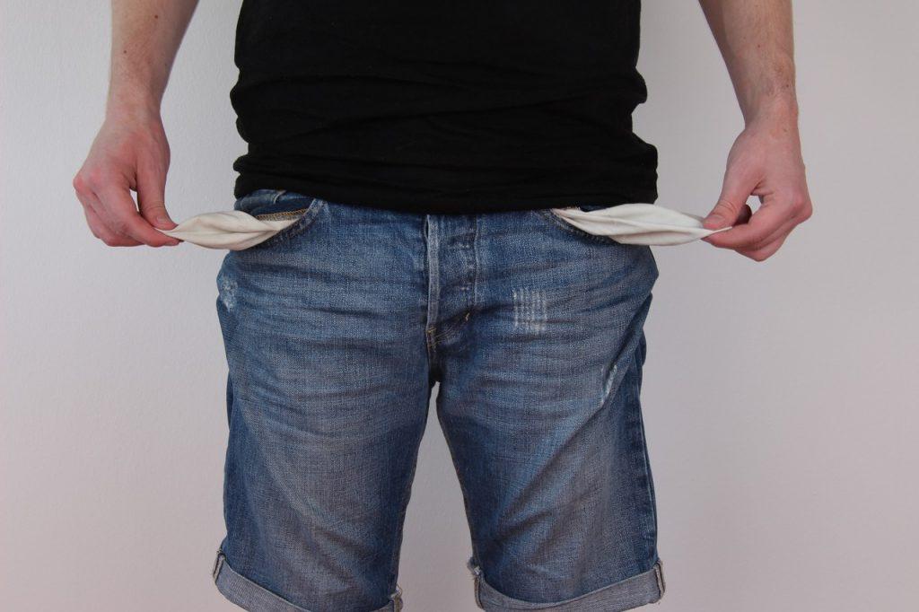 Ein Mann zeigt seine leeren Hosentaschen, indem er das Innenfutter rauszieht