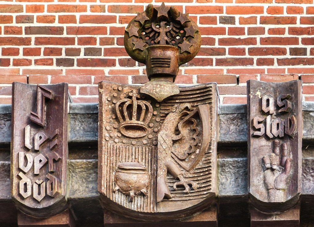 """Ostfriesischer Wahlspruch rechts und links von einem Wappen: """"Lever dod as Slav"""""""