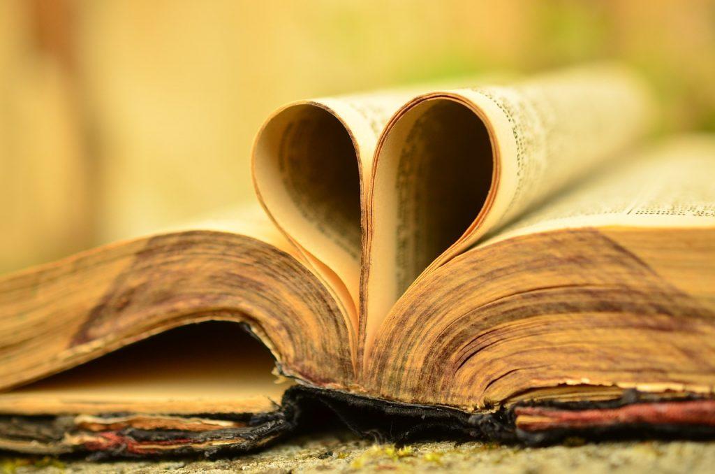 Eine alte Bibel, deren Blätter zu einem Herz geformt sind
