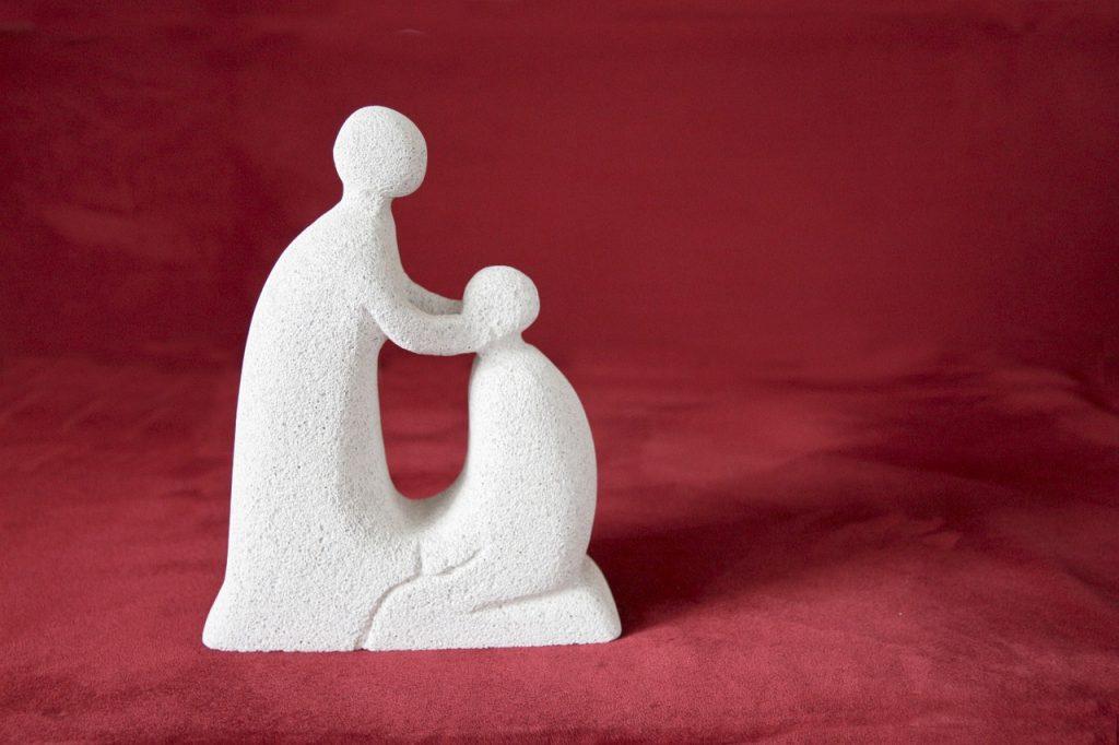 Schlichte Skulptur eines Menschen, der einen anderen segnet