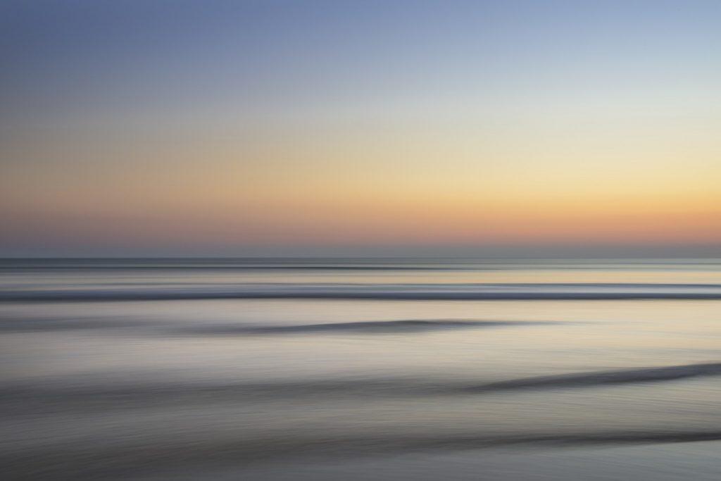 Meer fast ohne Wellen mit zarter Abend- oder Morgenröte