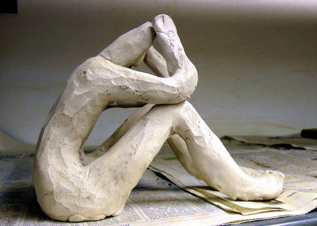 Tonfigur eines Töpfers auf Zeitungspapier, sitzt mit angewinkelten Knien und stützt den Kopf in die Hände