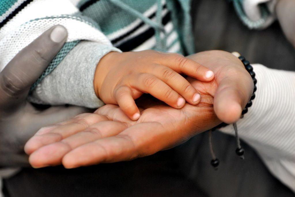 Hand eines Kindes in der Hand der Eltern