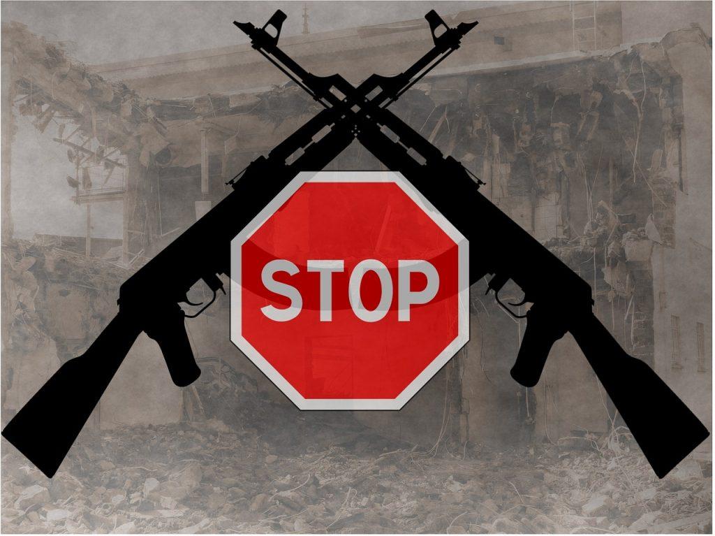 Abrüstungssymbolik: ein Stopp-Schild vor zwei gekreuzten Gewehren