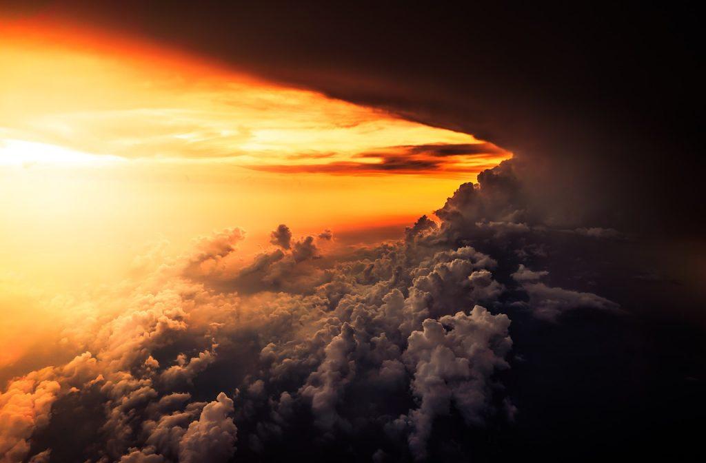 Wolkenlandschaft bei Sonnenaufgang - Licht bricht von der Seite in ein dunkles Wolkenfeld herein