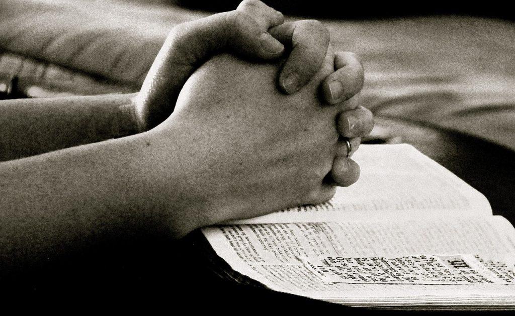 Zum Beten gefaltete Hände auf einer geöffneten Bibel