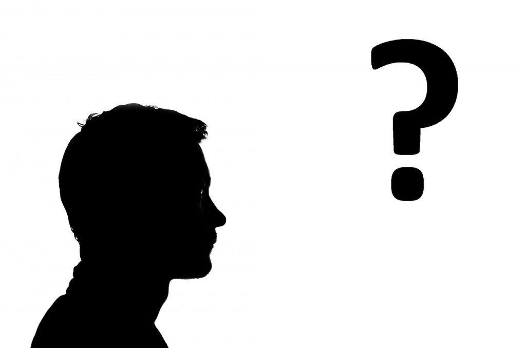 Silhouette eines jungen Mannes, der auf ein großes Fragezeichen blickt