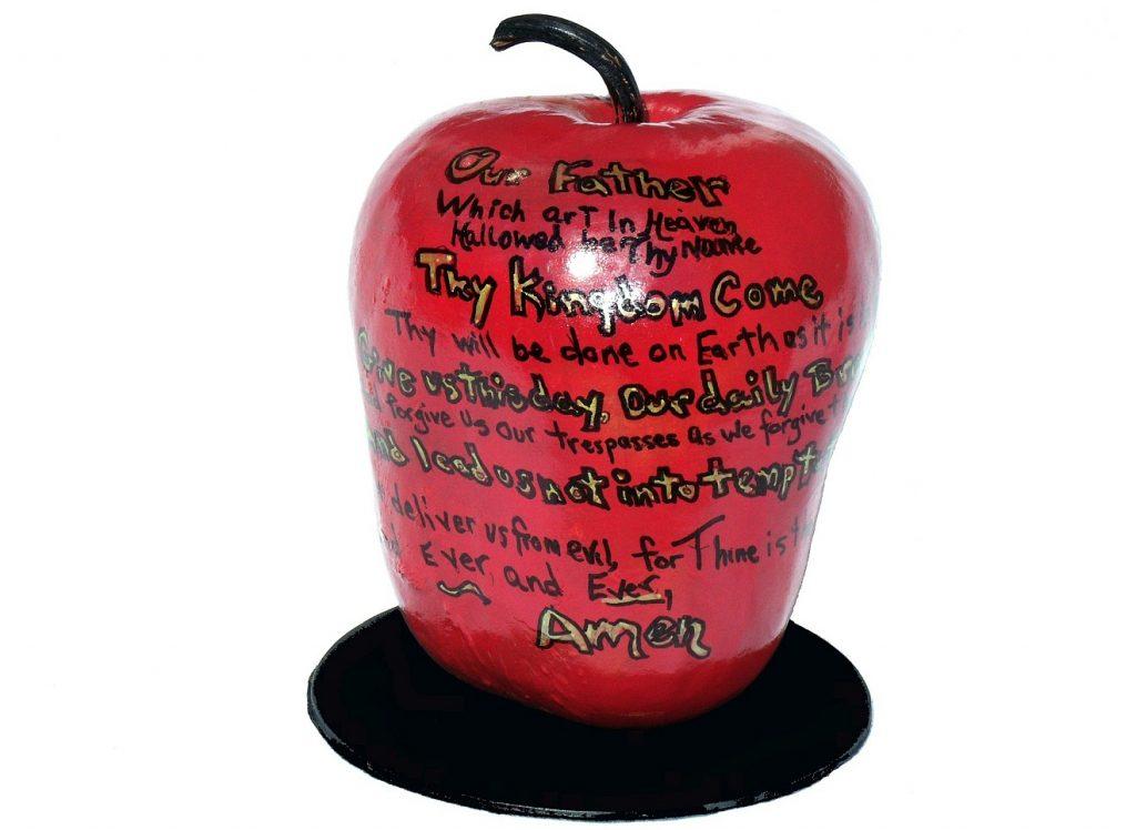 Ein roter Apfel, auf dem das Vaterunser auf Englisch draufsteht