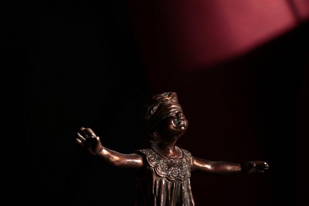 Statue of a blind person with wide outstretched arms in the dark, a faint light is to be seen in the top right corner